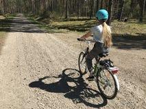 Ragazza che guida una bici in campagna polacca immagine stock