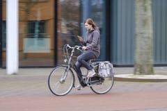 Ragazza che guida una bici e gli sguardi al suo smartphone, il pericolo Immagine Stock Libera da Diritti