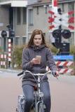 Ragazza che guida una bici e gli sguardi al suo smartphone, il pericolo Fotografia Stock