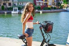 Ragazza che guida una bici che sorride nel Mediterraneo fotografia stock
