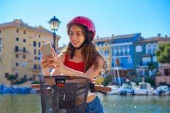 Ragazza che guida una e-bici pieghevole in un porticciolo Mediterraneo fotografie stock libere da diritti