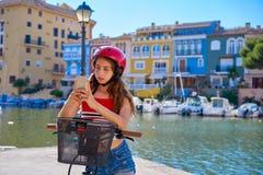Ragazza che guida una e-bici pieghevole in un porticciolo Mediterraneo fotografia stock libera da diritti
