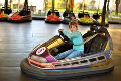 Ragazza che guida una macchina in un parco di divertimenti fotografia stock
