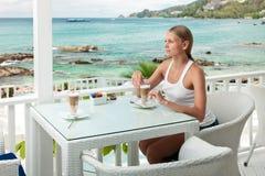 Ragazza che ha intervallo per il caffè in un caffè di vista di oceano Fotografia Stock Libera da Diritti