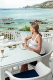 Ragazza che ha intervallo per il caffè in un caffè di vista di oceano Immagine Stock