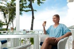Ragazza che ha intervallo per il caffè in un caffè di vista di oceano Immagine Stock Libera da Diritti