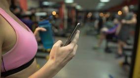 Ragazza che ha rottura dall'esercizio in palestra, controllante cellulare, bottiglia di acqua a disposizione archivi video