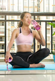 Ragazza che hidrating durante l'allenamento a casa Fotografie Stock Libere da Diritti