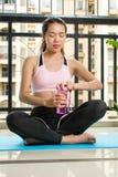 Ragazza che hidrating durante l'allenamento a casa Fotografia Stock Libera da Diritti