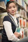 Ragazza che huggering un libro vicino allo scaffale per libri Fotografia Stock Libera da Diritti