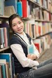 Ragazza che huggering un libro vicino allo scaffale per libri Fotografia Stock