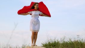 Ragazza che imbroglia intorno stare su un campo in un mantello rosso, giocante supereroe la donna allegra gioca in un mantello ro video d archivio