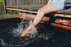 Ragazza che immerge i piedi nell'acqua e nella risata Immagine Stock