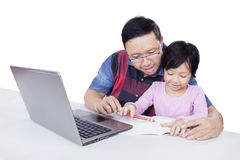 Ragazza che impara con il padre che per mezzo di un libro e di un computer portatile Fotografie Stock Libere da Diritti