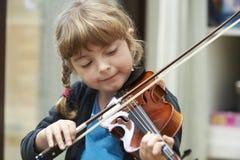 Ragazza che impara giocare violino fotografie stock