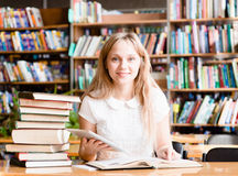 Ragazza che impara nella biblioteca e che legge libro elettronico sul computer della compressa Immagine Stock