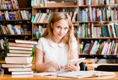 Ragazza che impara nella biblioteca e che legge libro elettronico sul computer della compressa Fotografia Stock