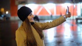 Ragazza che indica dito sullo smartphone dello schermo sulla luce di colore del bokeh di illuminazione del fondo nella città atmo stock footage