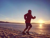 Ragazza che indossa abiti sportivi neri rossi e funzionamento sulla neve fotografia stock libera da diritti