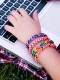 Ragazza che indossa i braccialetti variopinti del telaio Fotografie Stock
