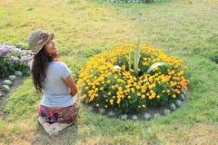 Ragazza che kneeing davanti ai fiori Fotografia Stock Libera da Diritti
