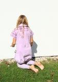 Ragazza che kneeing in parete bianca anteriore Immagini Stock Libere da Diritti