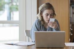 Ragazza che lavora ad un computer portatile e ad un telefono Immagine Stock Libera da Diritti