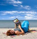 Ragazza che lavora al computer portatile vicino del mare fotografie stock libere da diritti