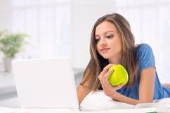 Ragazza che lavora con il computer portatile nel paese che tiene una mela Immagine Stock Libera da Diritti