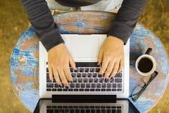 Ragazza che lavora con il computer portatile su una tavola di legno d'annata Fotografie Stock Libere da Diritti