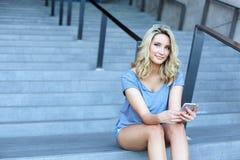 Ragazza che lavora con il telefono cellulare e che si siede sulle scale Fotografie Stock