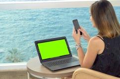 Ragazza che lavora con un taccuino sul terrazzo di un hotel che esamina il mare verde chiave di intensità immagini stock libere da diritti