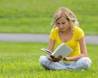 Ragazza che legge il libro. Bella giovane donna bionda con il libro che si siede sull'erba. All'aperto. Giorno soleggiato. Fotografie Stock Libere da Diritti