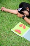 Ragazza che legge il libro di cuore sull'erba immagini stock