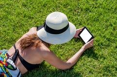 Ragazza che legge libro elettronico sull'erba fotografia stock