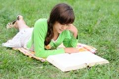 Ragazza che legge un libro che si trova sull'erba Fotografia Stock Libera da Diritti