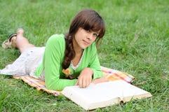 Ragazza che legge un libro che si trova sull'erba Immagine Stock Libera da Diritti