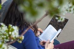 Ragazza che legge un libro e un uomo che lavorano al PC Fotografia Stock