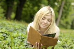 Ragazza che legge un libro esterno. Fotografia Stock Libera da Diritti