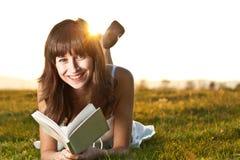 Ragazza che legge un libro esterno Immagine Stock