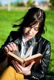 Ragazza che legge un libro un giorno di molla soleggiato in natura immagini stock