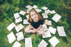 Ragazza che legge un libro mentre trovandosi nell'erba Una ragazza fra i libri nel giardino di estate Immagine Stock
