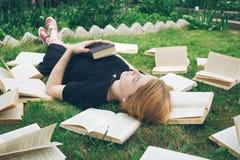 Ragazza che legge un libro mentre trovandosi nell'erba Una ragazza fra i libri nel giardino di estate Fotografia Stock