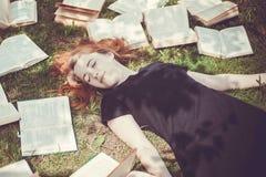Ragazza che legge un libro mentre trovandosi nell'erba Una ragazza fra i libri nel giardino di estate Immagine Stock Libera da Diritti