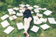 Ragazza che legge un libro mentre trovandosi nell'erba Una ragazza fra i libri nel giardino di estate Immagini Stock