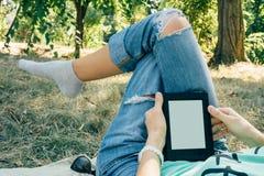 Ragazza che legge un libro nel parco di estate che si trova sulla terra sotto Fotografia Stock Libera da Diritti