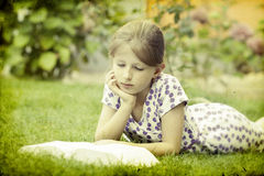 Ragazza che legge un libro nella sosta Fotografia Stock