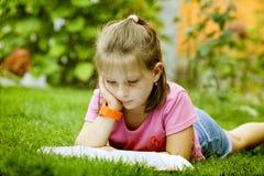 Ragazza che legge un libro nella sosta Immagini Stock