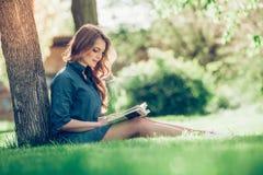 Ragazza che legge un libro in sosta Immagini Stock