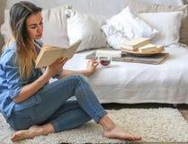 Ragazza che legge un libro in una stanza accogliente Immagini Stock Libere da Diritti